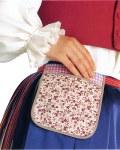 Kuva Keuruun naisen kansallispuvun kupeelta, taskun kiinnittimenä kapea pirtanauha (Kuvan lähde: http://www.kansallispuvut.fi)