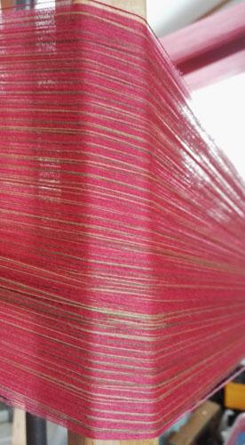 Uskelan kansallispuvun liivikankaan loimi on pääasiassa vadelmanpunainen.